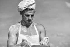 Chef cook preparing dough for baking. Cook or chef with muscular shoulders and chest mixing flour in bowl. Cookery. Concept. Man on confident face wears cooking stock photo