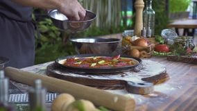 Chef cook preparing pizza with sausage and tomatoes on kitchen table, food background. Italian pizzaillo making pizza in stock video