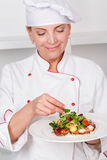 Chef-cook presenting meals. Beautiful mature female cook holding a plate and serving octopus salad with mash-salad Royalty Free Stock Images