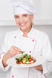 Chef-cook presenting meals. Beautiful mature female cook holding a plate and serving octopus salad with mash-salad smiling at a camera Royalty Free Stock Photography