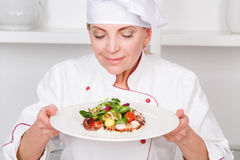 Chef-cook presenting meals. Close-up of an attractive female cook holding a plate with octopus salad and joyfully smelling it Royalty Free Stock Image
