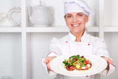 Chef-cook presenting meals. Selective focus on fresh octopus salad which a smiling female cook stretching out to the camera Stock Image