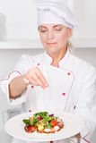 Chef-cook presenting meals. Selective focus on plate with octopus salad and a female cook sprinkling it with spices Stock Image