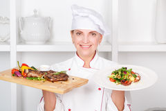 Chef-cook presenting meals. Smiling attractive female cook holding in one hand a cutting board with fried meat steak with vegetables grill and a plate with fresh Stock Photos