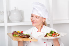 Chef-cook presenting meals. Smiling attractive female cook holding in one hand a cutting board with fried meat steak with vegetables grill and fresh octopus Stock Images