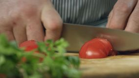 Chef cook professionally cutts tomatoes with a chef`s knife on cutting board stock video footage