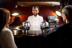 Chef cook serving dishes to the couple Royalty Free Stock Photo