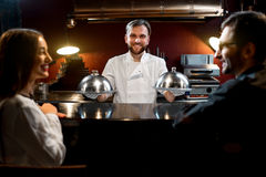Chef cook serving dishes to the couple Stock Photography