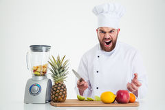 Chef cook sitting at the table with fruits Royalty Free Stock Photos