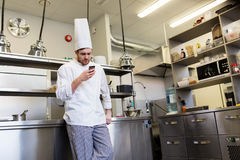 Chef cook with smartphone at restaurant kitchen Stock Images
