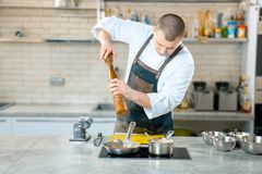 Chef cook standing and cooking in frying pan on the kitchen stock photo