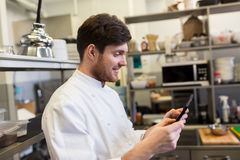 Chef cook with tablet pc at restaurant kitchen. Cooking, profession and people concept - happy male chef cook with tablet pc computer at restaurant kitchen Stock Photography