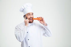 Chef cook talking on the phone and eating carrot royalty free stock photo