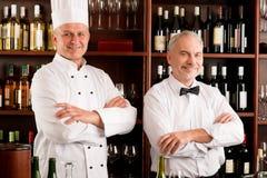 Chef cook and waiter restaurant wine bar. Chef cook and waiter smiling in restaurant wine bar stock photo