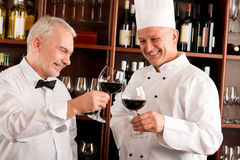 Chef cook and waiter wine tasting restaurant Stock Photos