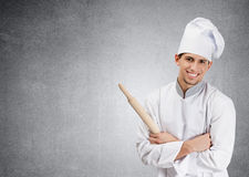Chef cook with wooden rolling pin on grey Royalty Free Stock Photo