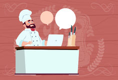 Chef Cook Working At Laptop Computer Cartoon Restaurant Chief In White Uniform Sit At Desk Over Wooden Textured. Background Flat Vector Illustration Stock Images