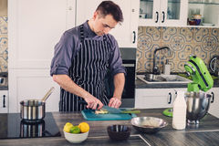 Chef cook working on a modern kitchen at home Royalty Free Stock Images