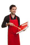 Chef cookbook. A smiling chef looking at the camera and pointing to a cookbook with a spoon Royalty Free Stock Images