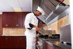 Chef cooking. A young male professional chef cooking food in commercial kitchen Royalty Free Stock Photo