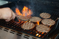 Chef is cooking burgers on gas grill Stock Photo