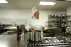 Chef cooking and delegating team. A chef cooking in a professional kitchen Royalty Free Stock Photos