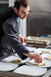 Chef cooking for dinner. Young chef in hotel or restaurant kitchen cooking for dinner Royalty Free Stock Images