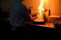 Chef cooking and doing flambe on food. In restaurant kitchen Stock Images