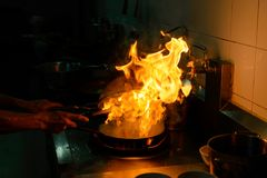 Chef cooking and doing flambe on food in kitchen Royalty Free Stock Photo