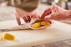 Chef cooking dorado fish. Royalty Free Stock Photo