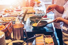 Chef are cooking food in a pan. Chef cooking on the Electric stove Royalty Free Stock Photography