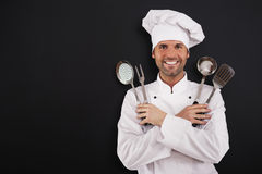 Chef with cooking equipment. Happy young chef with cooking equipment Royalty Free Stock Photo