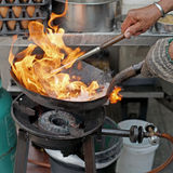 Chef cooking with fire in frying pan Royalty Free Stock Photography