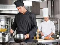 Chef Cooking Food With Colleague Chopping Royalty Free Stock Photography