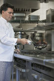 Chef Cooking Food In Kitchen Stock Photography