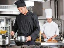 Chef-Cooking Food With-Kollege-Hacken Lizenzfreie Stockfotografie
