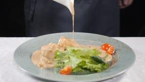 Chef Cooking Frau in der Küche Strömende Sahnesauce des Kochers auf Teller mit Kammmuscheln und neuer Mischung des Kopfsalates un stock video footage