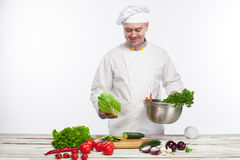 Chef cooking fresh vegetable salad in his kitchen Stock Photography