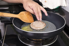 Chef cooking Hamburger on the pan Royalty Free Stock Image