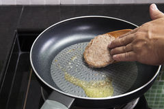 Chef cooking Hamburger on the pan Stock Photography
