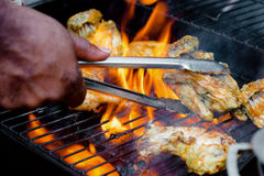 Chef cooking jerk barbecue BBQ chicken on the grill hand turning food.  Stock Photos