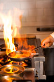 Chef cooking in kitchen stove. Chef cooking with flame in a frying pan on a kitchen stove Stock Photo