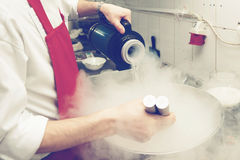 Chef is cooking with liquid nitrogen, toned. Chef is cooking ice cream with liquid nitrogen, toned image Royalty Free Stock Images