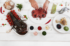 Chef cooking octopus in kitchen, flat lay Royalty Free Stock Photography