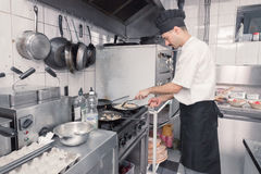 Chef cooking omlette pans cooker kitchen. One young adult man, chef cooking omelet omelette pans cooker kitchen, professional commercial kitchen Royalty Free Stock Images