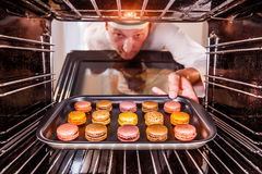 Chef cooking in the oven. Chef prepares macarons in the oven, view from the inside of the oven. Cooking in the oven Stock Photos