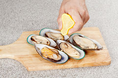Chef cooking oysters with lemon. Chef cooking fresh oysters with lemon on cutting board Stock Images