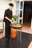 Chef cooking paella in the second stage crabs and squid rings Royalty Free Stock Photography