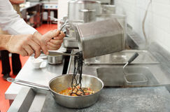 Chef is cooking pasta at commercial kitchen Royalty Free Stock Photos