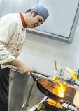 Chef Cooking Pasta. Image of a chef cooking pasta in a restaurant kitchen. Selective focus on the pan Royalty Free Stock Photo